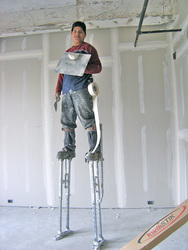 standing on metal stilts, working with sheetrock