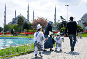 Turkish family with their sons in circumsicion outfits.
